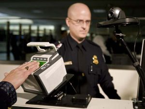 "Department of Homeland Security(DHS) Officer Brian Pittack stands at his station with a new 10-fingerprint scanner(foreground) for international arriving passengers 10 December 2007 at Dulles International Airport in Dulles,Virginia. Foreigners who entered the United States at Dulles airport, near Washington, were required to give officials 10 fingerprints instead of two, as new security measures were rolled out Monday. ""This is a more secure system that improves safety for everybody,"" Secretary of Homeland Security Michael Chertoff told a news conference at the airport. Most foreigners aged between 14 and 79 who travel to the United States have been required since 2004 to provide the prints of two fingers and a digital photograph to US officials, either when they apply for a visa or arrive in the United States. AFP PHOTO/PAUL J.RICHARDS (Photo credit should read PAUL J. RICHARDS/AFP/Getty Images)"